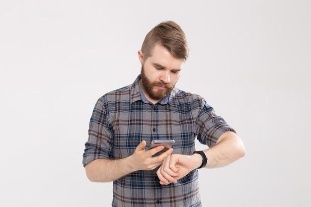 Homem barbudo verifica os resultados da aptidão em fundo branco. adulto usando pulseira de rastreador esportivo