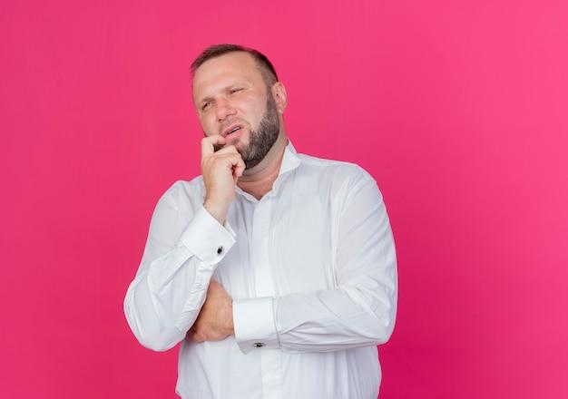 Homem barbudo vestindo camisa branca e olhando de lado perplexo em pé na parede rosa