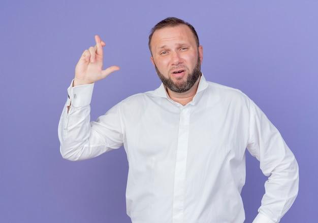 Homem barbudo vestindo camisa branca fazendo uma promessa cruzando os dedos em pé sobre a parede azul