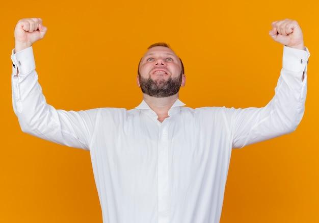 Homem barbudo vestindo camisa branca levantando os punhos e comemorando seu sucesso em pé sobre a parede laranja