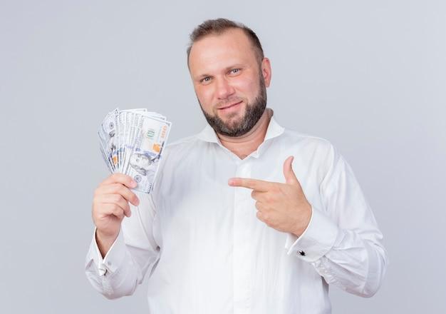 Homem barbudo vestindo camisa branca segurando dinheiro apontando com o dedo indicador para o dinheiro, sorrindo confiante em pé sobre uma parede branca
