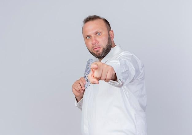 Homem barbudo vestindo camisa branca segurando dinheiro e escondendo dinheiro apontando com o dedo indicador para você em pé sobre uma parede branca