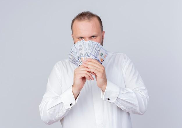 Homem barbudo vestindo camisa branca segurando dinheiro e sorrindo maliciosamente em pé sobre uma parede branca