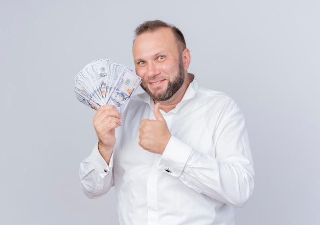 Homem barbudo vestindo camisa branca segurando dinheiro e sorrindo maliciosamente mostrando os polegares em pé sobre uma parede branca
