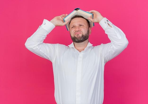 Homem barbudo vestindo camisa branca segurando um livro aberto acima da cabeça, e está descontente e confuso em pé sobre uma parede rosa