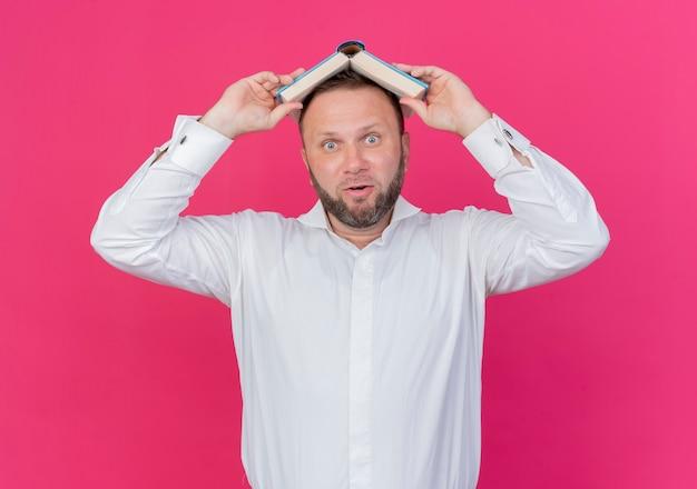 Homem barbudo vestindo camisa branca segurando um livro aberto sobre a cabeça e sendo surpreendido em pé na parede rosa