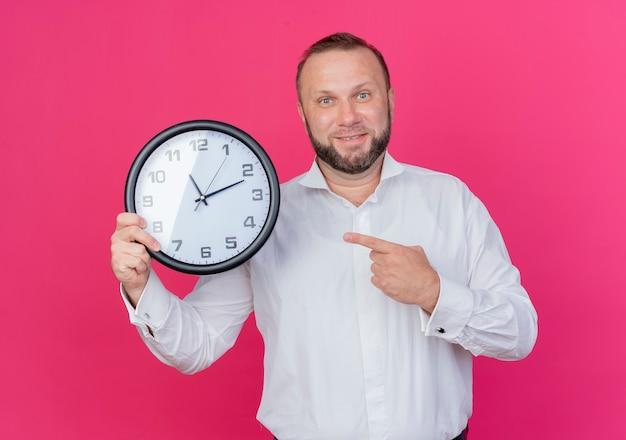 Homem barbudo vestindo camisa branca segurando um relógio de parede apontando com o dedo para ele e sorrindo em pé sobre a parede rosa
