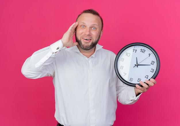 Homem barbudo vestindo camisa branca segurando um relógio de parede parecendo confuso sorrindo em pé sobre a parede rosa