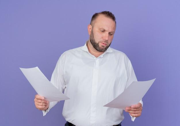 Homem barbudo vestindo uma camisa branca segurando folhas de papel em branco, olhando para elas com uma cara séria em pé sobre a parede azul