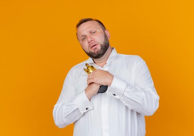Homem barbudo, vestindo uma camisa branca, segurando um troféu com uma cara infeliz em pé sobre a parede laranja