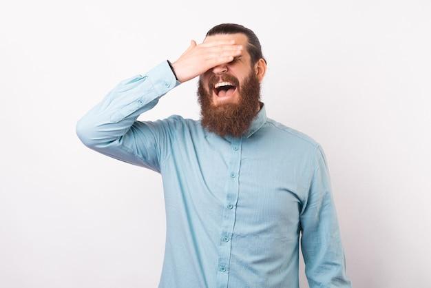 Homem barbudo, vestindo uma camisa, está fazendo um gesto no rosto com a palma da mão.