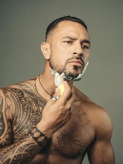 Homem barbudo visitando o cabeleireiro na barbearia. homem de barba cortando cabelo de cabeleireiro na barbearia.