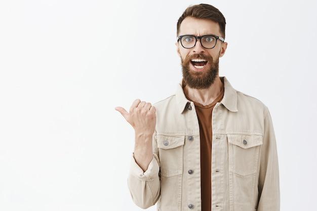 Homem barbudo zangado e confuso de óculos posando contra a parede branca