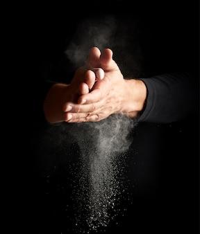 Homem bate palmas e espalha para o lado uma substância branca sobre um fundo preto