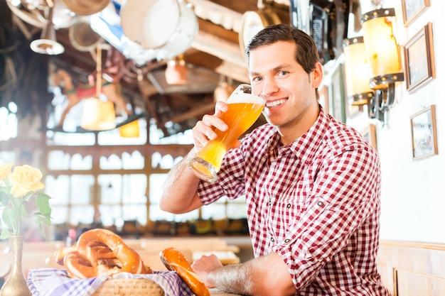 Homem bávaro bebendo cerveja de trigo