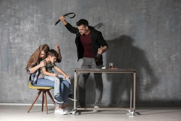 Homem bêbado ameaçando esposa e filho contra parede cinza
