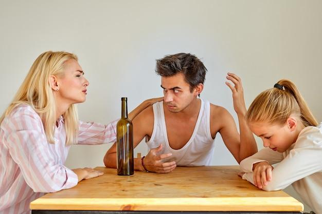 Homem bêbado brigando com a esposa, sentado na cozinha à mesa com a filha deprimida