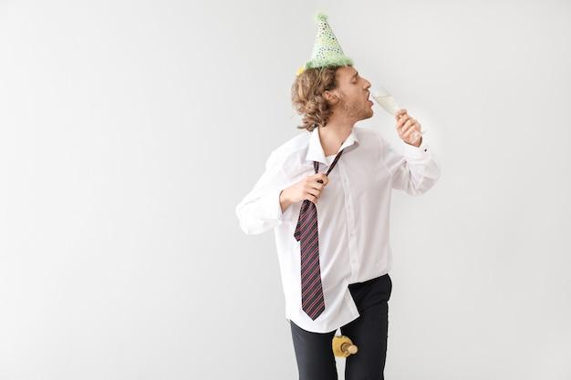 Homem bêbado com chapéu de festa e vinho na luz