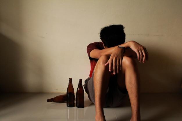 Homem bêbado com garrafa de cerveja está tendo estresse na vida e sentado sozinho em um quarto vazio, triste, solitário, chool, adolescência, violência doméstica, problemas amorosos indesejados, sozinho, família
