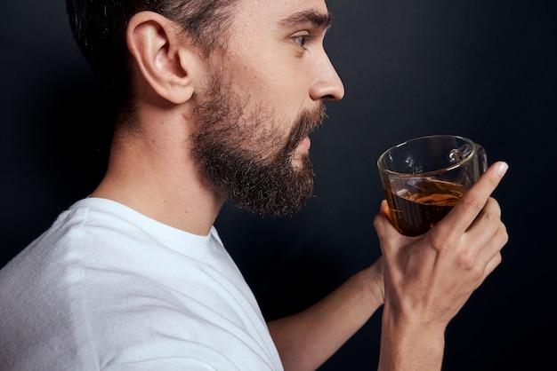 Homem bêbado com uma caneca de cerveja, vestindo uma camiseta branca em um fundo escuro. visualização recortada.