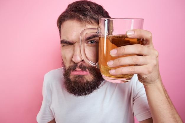 Homem bêbado com uma caneca grande de cerveja em um espaço rosa e uma camiseta branca visão descontraída de uma barba espessa