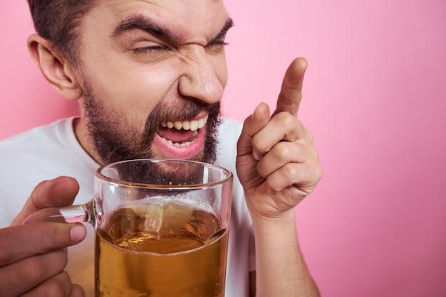 Homem bêbado com uma caneca grande de cerveja em um fundo rosa e uma visão relaxada de camiseta branca de um retrato de bigode de barba espessa. foto de alta qualidade