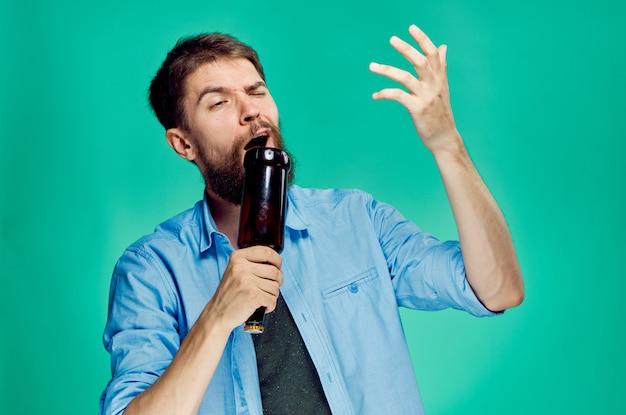 Homem bêbado com uma garrafa de cerveja na mão retrata um fundo verde cantando