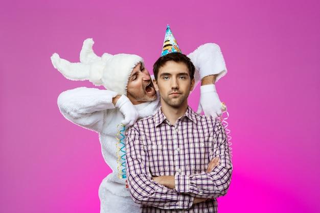 Homem bêbado e coelho na festa de aniversário sobre parede roxa.
