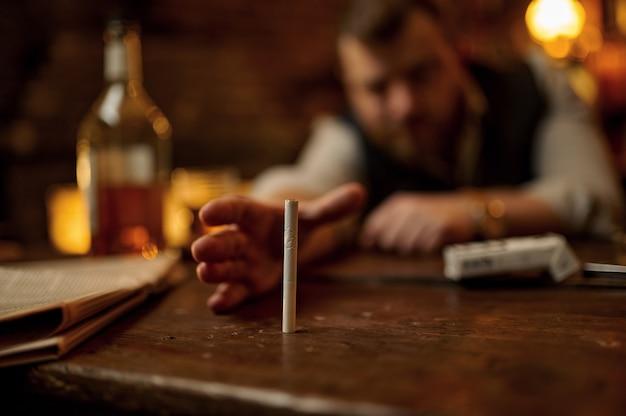Homem bêbado tenta pegar um cigarro, bebida alcoólica em garrafa no fundo. cultura de fumar tabaco, sabor específico. fumante masculino com maus hábitos e vícios