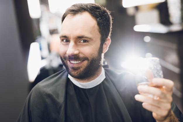 Homem bebe álcool na poltrona de cabeleireiro de uma barbearia