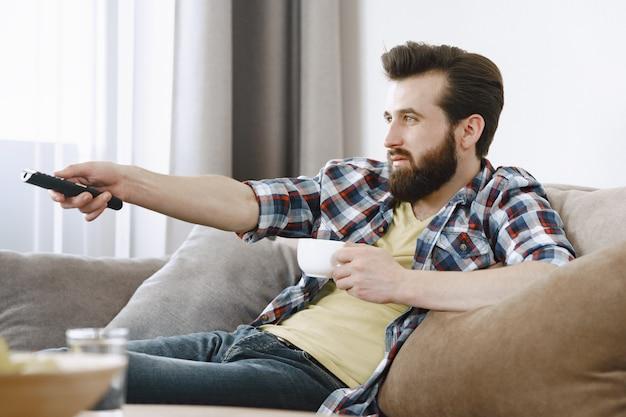 Homem bebe café. cara assistindo tv no sofá. controle remoto da tv nas mãos.