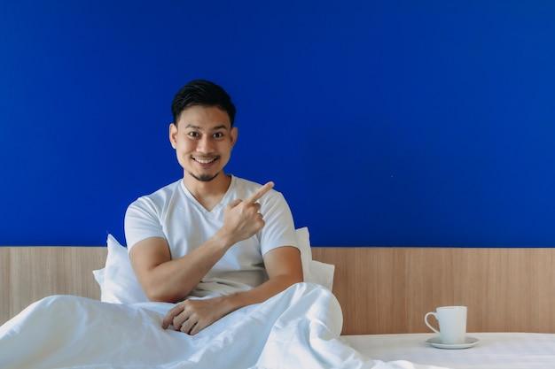 Homem bebe café da manhã na cama com fundo de tela azul