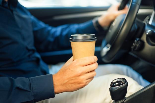 Homem bebe café dentro do carro