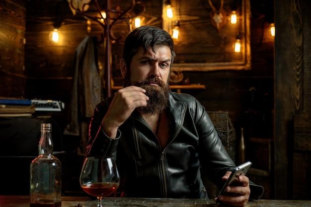 Homem bebe conhaque ou homem barbudo de terno e bebe conhaque de uísque ou sommelie de conhaque ...
