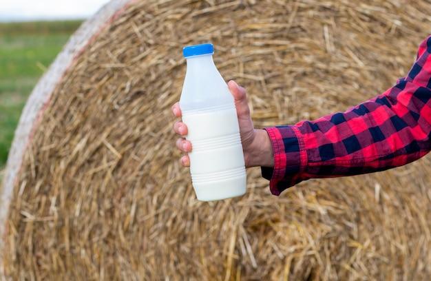 Homem bebe leite biológico fresco no campo, feno, grama, fazenda