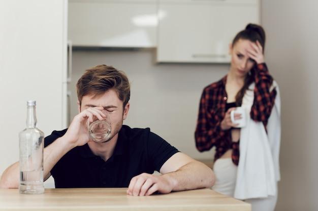 Homem bebe sentado à mesa da cozinha, uma mulher chateada fica ao lado de um homem e olha para ele