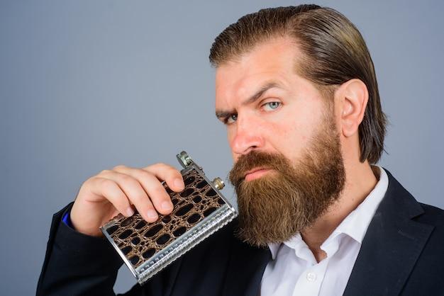 Homem bebe uísque de garrafa, garrafa de metal plana, para cara de álcool, segura uma garrafa de metal