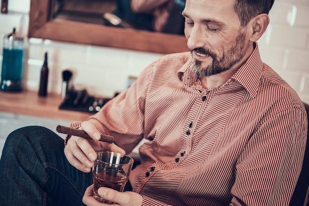 Homem bebe uísque e fuma um cigarro em uma barbearia