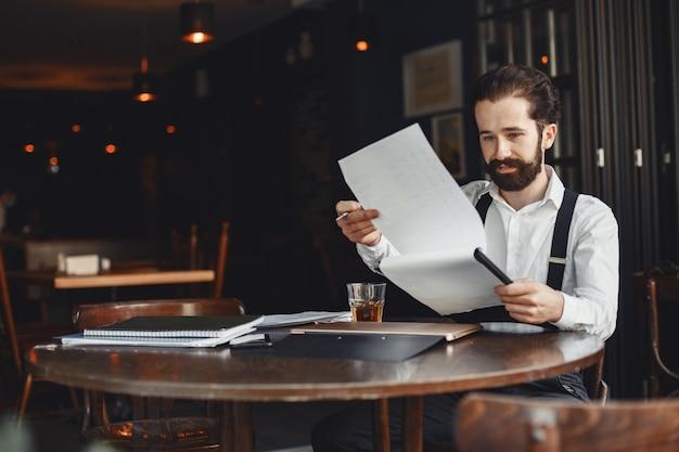 Homem bebe uísque. empresário lê documentos. diretor de camisa e suspensórios.