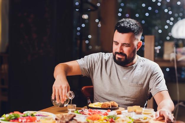 Homem bebe vodka em uma mesa grande com comida e lanches.