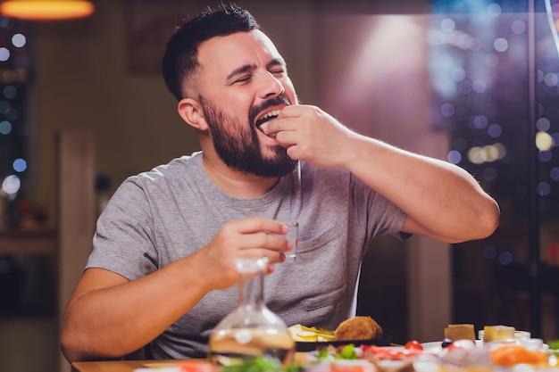 Homem bebe vodka em uma mesa grande com gordura de alimentos e lanches.