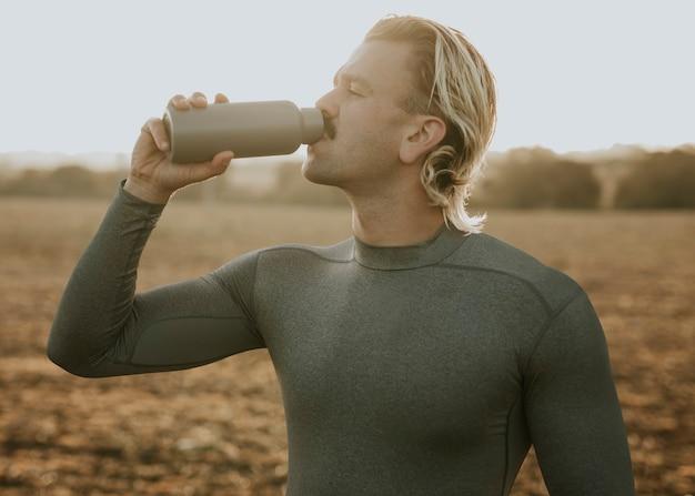 Homem bebendo água de uma garrafa de aço inoxidável após malhar