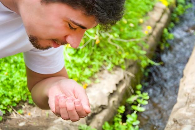 Homem bebendo água do córrego