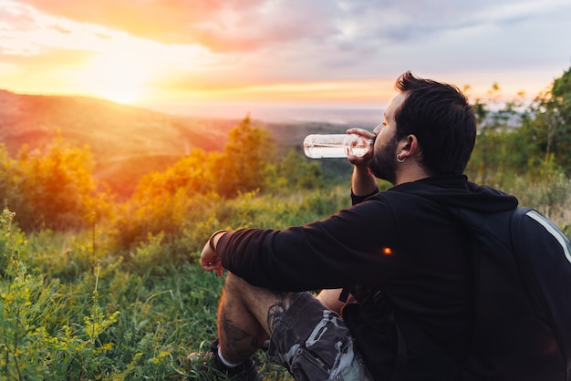 Homem bebendo água e apreciando o pôr do sol da montanha