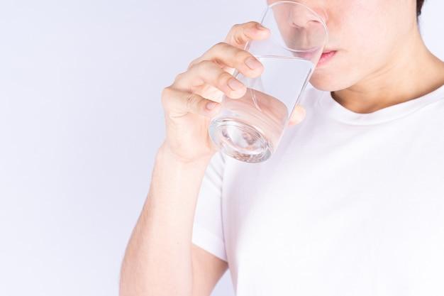 Homem bebendo água isolada de fundo cinza. água potável limpa em vidro transparente.