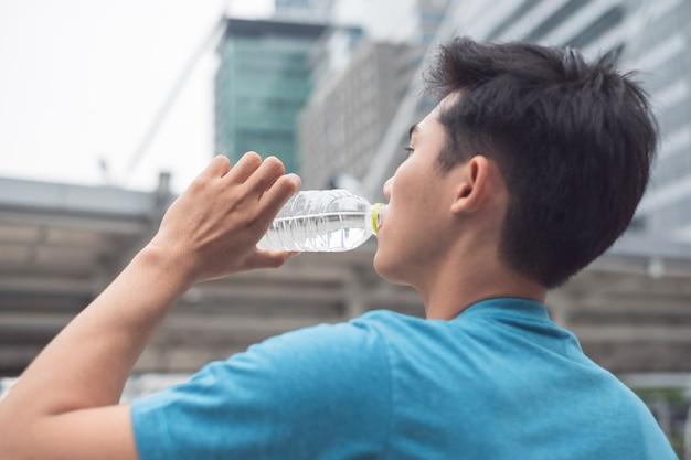 Homem bebendo água mineral após o término do exercício