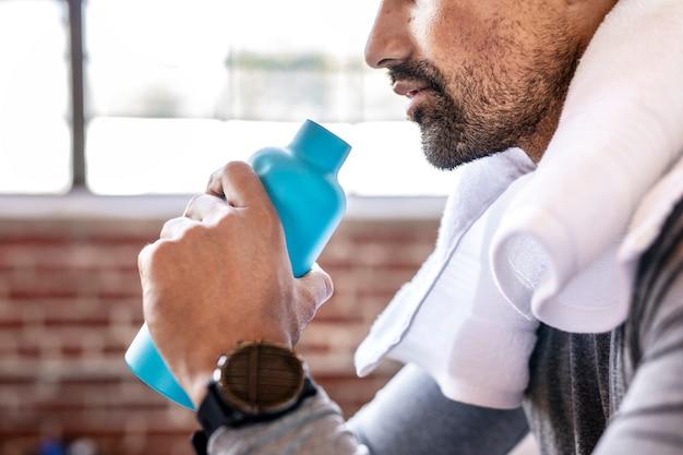 Homem bebendo água para hidratar