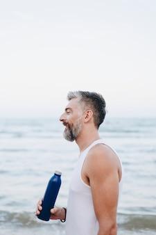 Homem bebendo água para reidratar