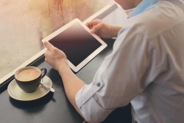 Homem, bebendo café e usando tablet no café com relaxante