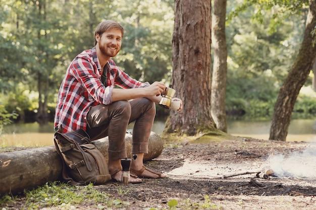Homem bebendo café na floresta
